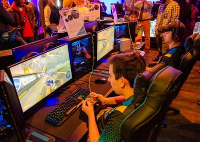 Students play at video game stations as guests look on