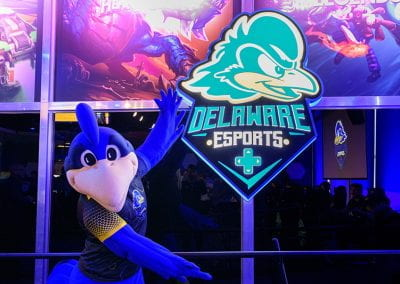 YoUDee poses in front of a Delaware Esports lit sign
