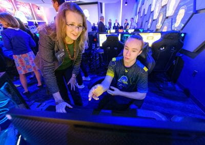 A student demonstrates a video game station to a female guest