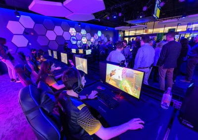 Students play at a row of video game stations as guests gather in the Esports Arena