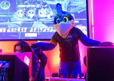 YoUDee stands behind students at gaming stations