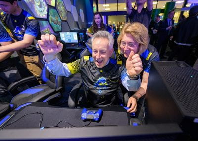 President Assanis cheers as he tries a video game while First Lady Assanis watches over his shoulder