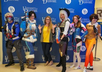 USC staff member poses with Overwatch cosplayers