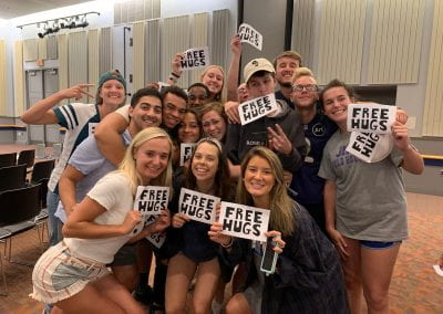"""QUEST Students holding signs that say """"Free Hugs"""""""