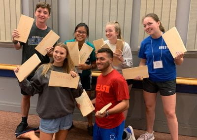 QUEST Students holding wooden boards that they broke in half