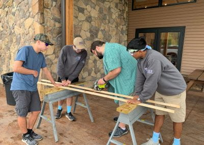 QUEST Students measuring and cutting wood