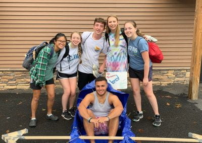 QUEST Students pose with a makeshift canoe