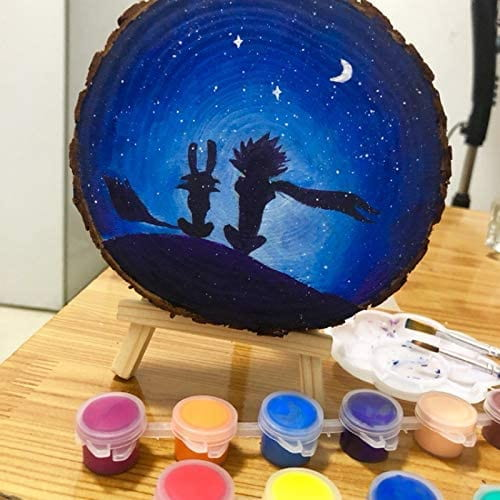 Circular cut of tree trunk with painting of two animal silhouettes against a starry background