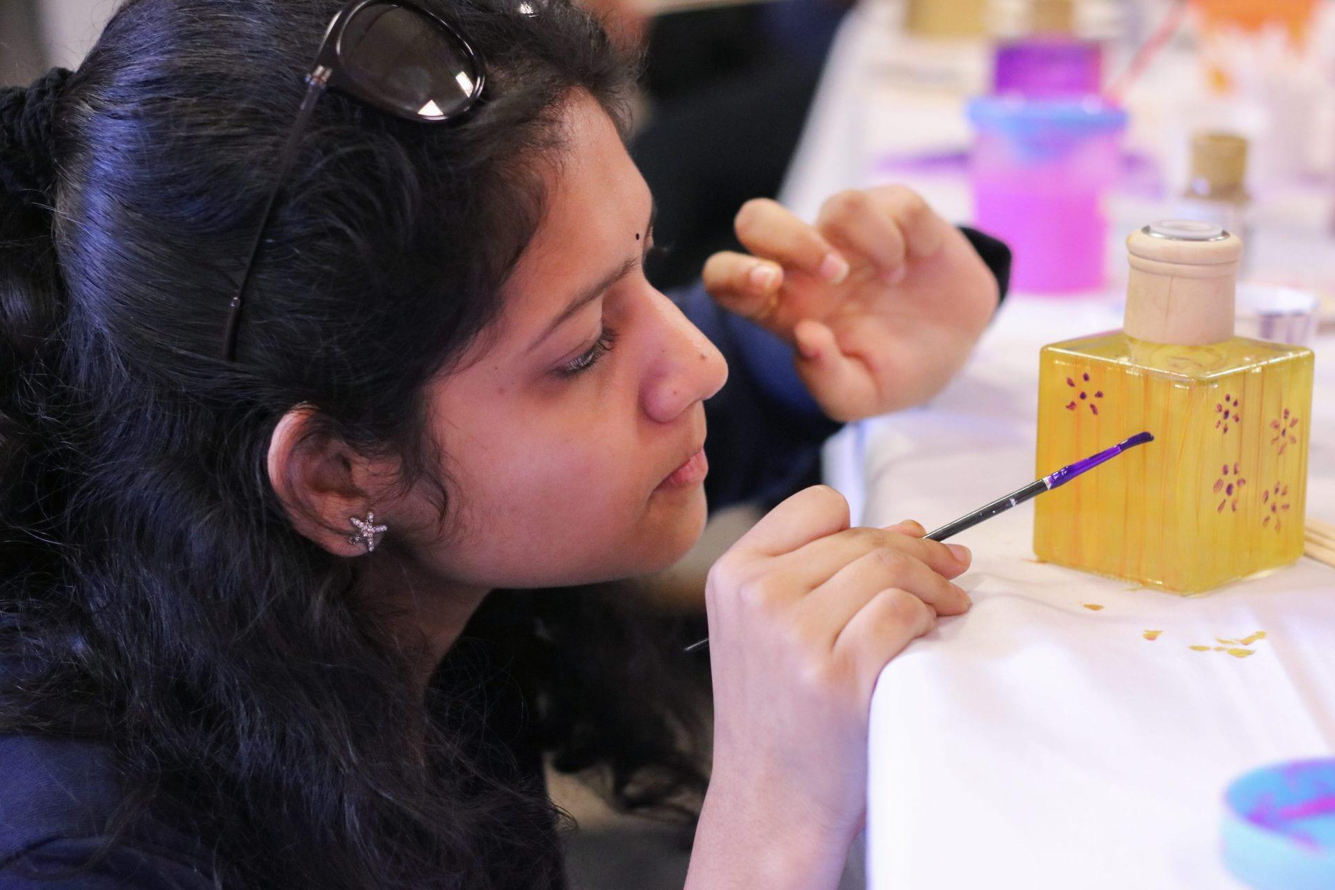 Student paints oil diffuser at USC Celebrates Diwali event.