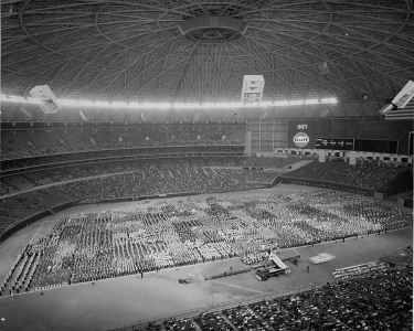 """Figure 3. AstroTurf was much more durable than natural grass, enabling stadium use for multiple functions. Here, bands assemble on the Astrodome's resilient AstroTurf surface. KUHT. """"Band day."""" 1953 - 2011. Online Image. University of Houston Digital Library. 26 March 2013. <http://digital.lib.uh.edu/u?/p15195coll38,237>"""
