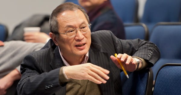 Dr. Yan seated in an auditorium, speaking with someone off camera.