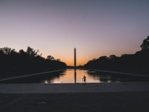 The Washington Monument in silhouette against a sunset across the reflecting pool.