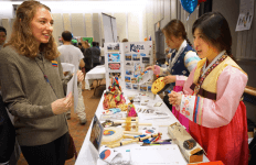 Students engage at the Korean culture fair table.