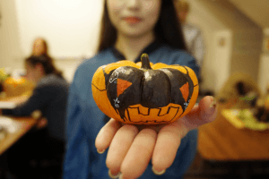 Student in an ELI classroom holding out a small decorated pumpkin