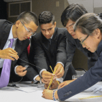 Students in professional clothing working as a team on a project.