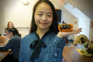 "Linhan ""Angelina"" Xu holds up her decorated mini pumpkin in Monica Farling's third-floor classroom at the ELI's building at 189 West Main Street."