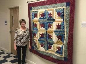 Tutor Nancy Blevins stands beside the quilt she made in honor of Patrick Ruffin.