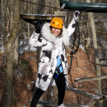 A student smiles while traversing a ropes course in the winter woods.
