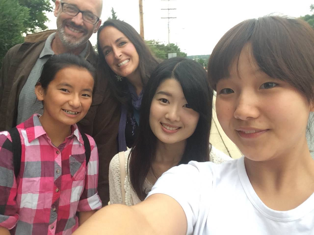 ELI student with her homestay hosts, all smiling for a group selfie