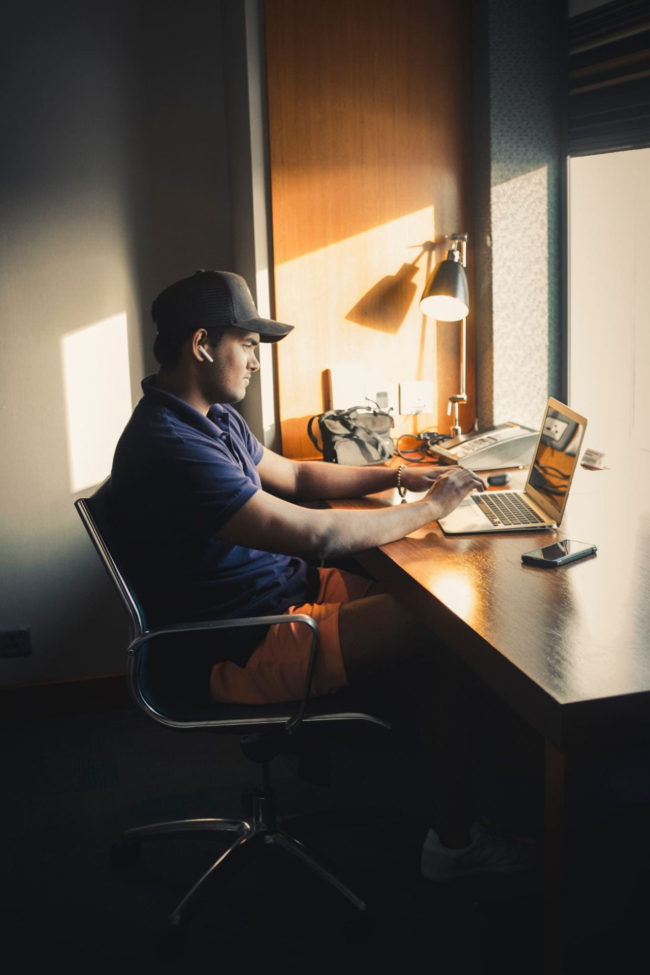 Person in a ballcap sits at a desk using a laptop