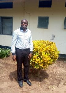 ELI alum Pius Kilasy stands outside on a sunny day. To his right is a small, yellow bush.