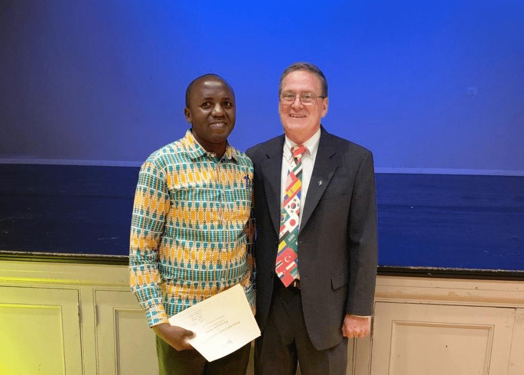 ELI alum Pius Kilasy holds his graduation certificate during an ELI graduation ceremony. To his left is ELI Director Scott Stevens.