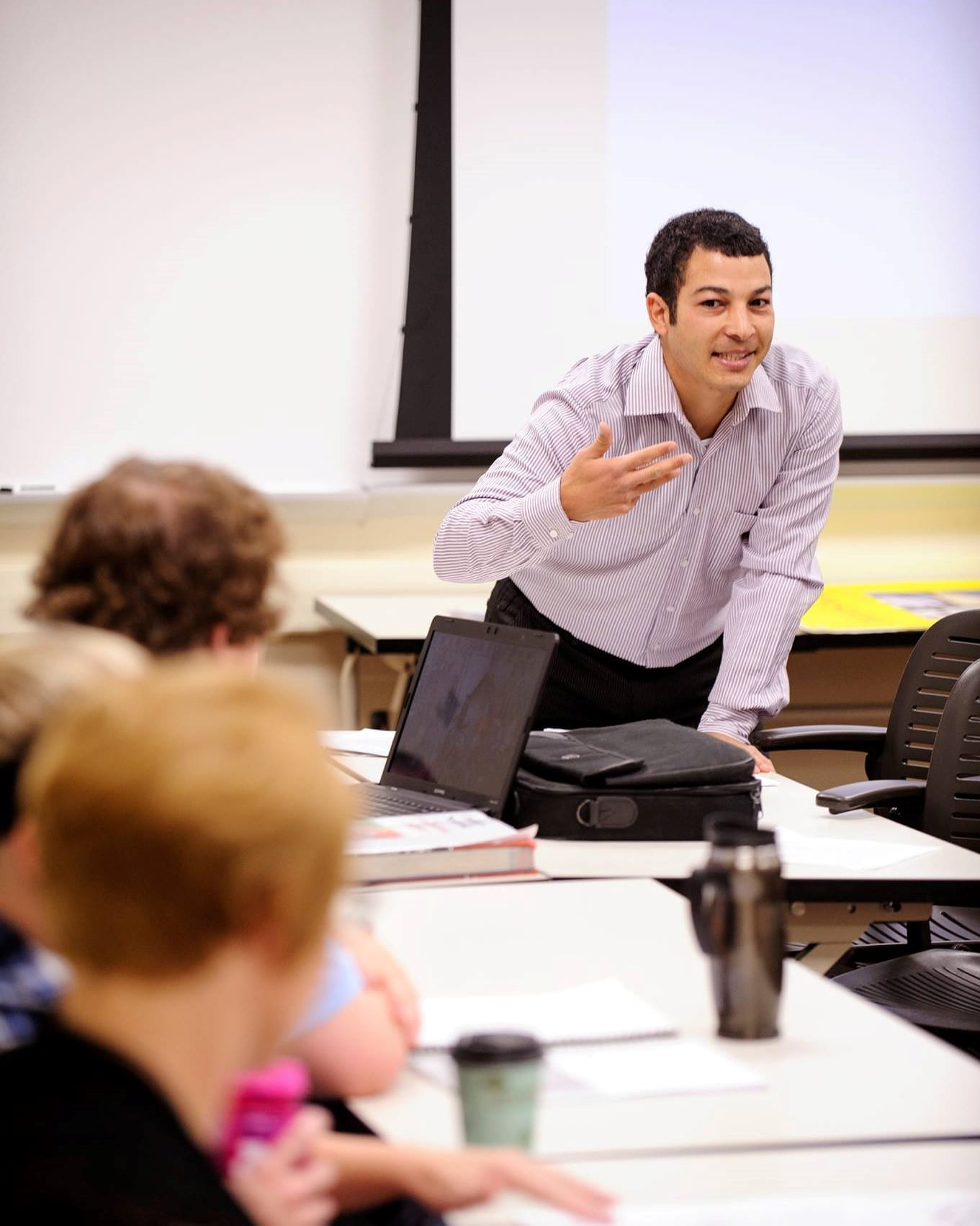 This photo shows Assistant Professor Adil Bentahar standing at the front of the classroom and gesturing to three students.