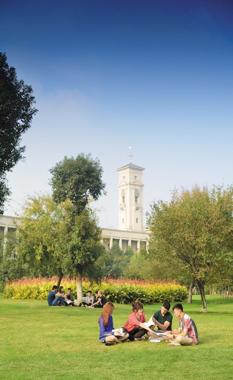 Students sit in circles on the lush lawns of UNNC