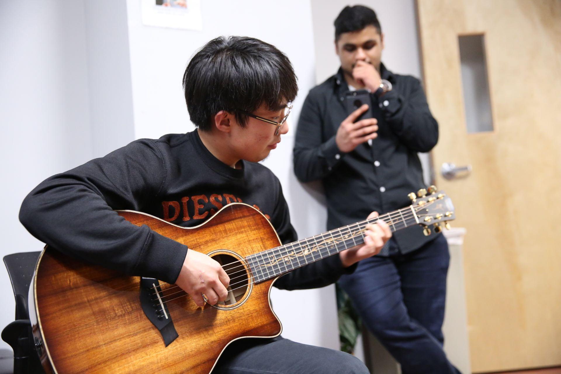 An ELI student plays guitar