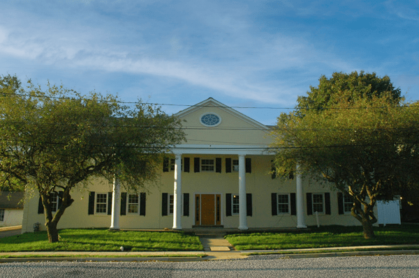 Two story yellow building with pediment and columns