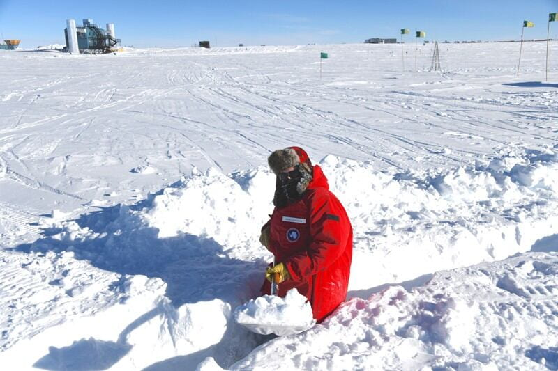 With the IceCube Laboratory in the distance, UD physicist Frank Schroeder shovels a trench for cables leading to a radio antenna he deployed at the South Pole in January 2020. Photos courtesy of Frank Schroeder, Alan Coleman and the IceCube Collaboration