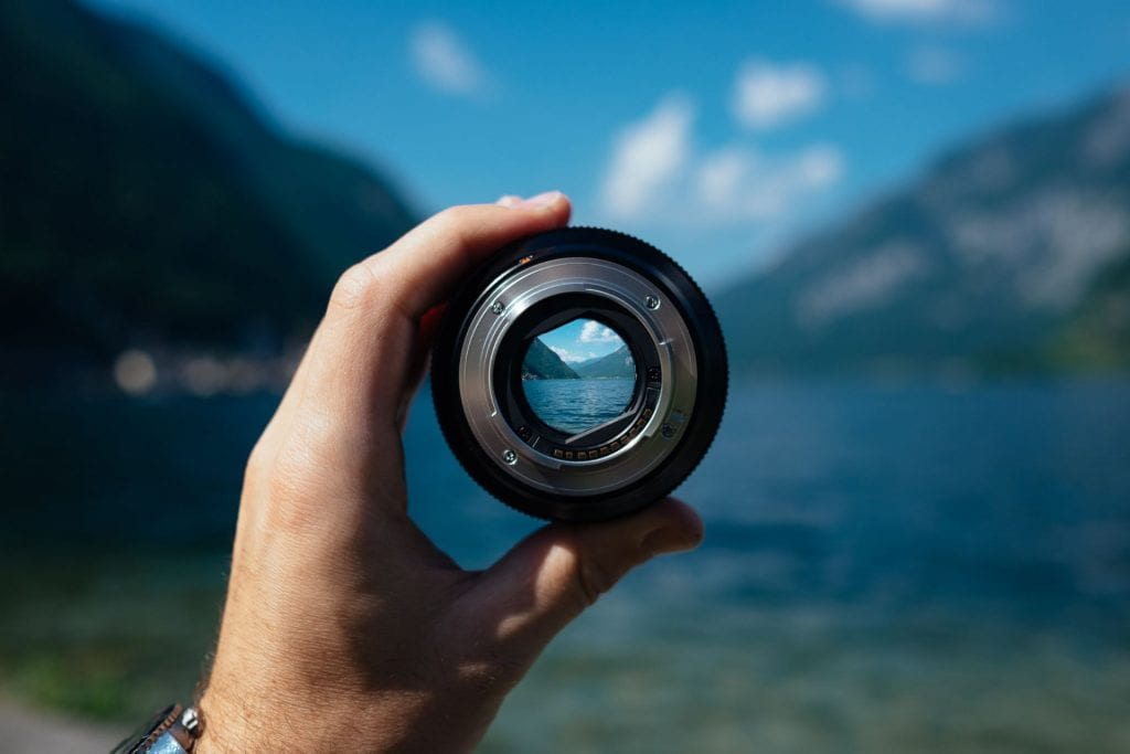 a hand holding a lens, with a focused landscape view inside