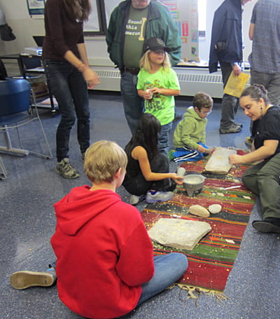 Children learn to grind grain the prehistoric way. Photo J. Waldbaum.