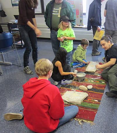 Children learn to grind grain the prehistoric way. Photo J. Waldbaum.