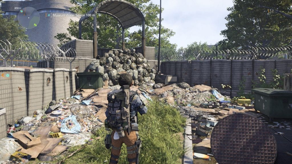 Player avatar looking at heaps of garbage near barbed wire and cement fences.