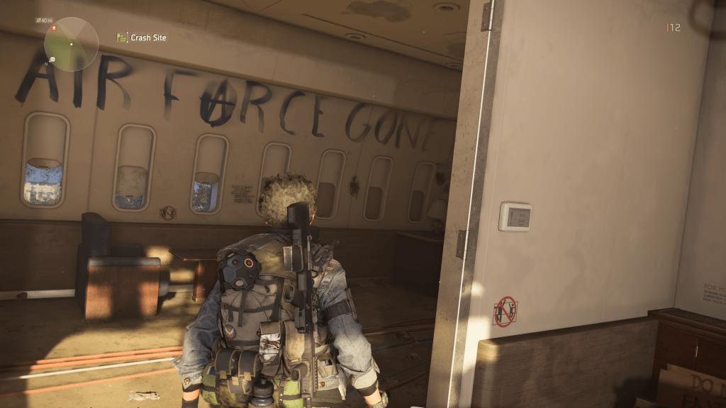 """Player avatar standing in the remains of Air Force One, the phrase """"Air Force One"""" spraypainted on the wall of the cabin and later edited to read """"Air Farce Gone."""" The A in """"farce"""" is drawn to look like the Anarchy symbol."""