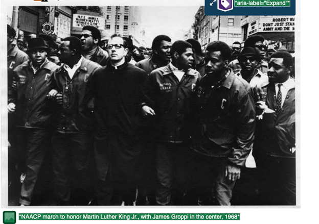 """A black-and-white photograph of a group of men walking through a city with the alt text """"NAACP march to honor Martin Luther King Jr., with James Groppi in the center, 1968"""""""