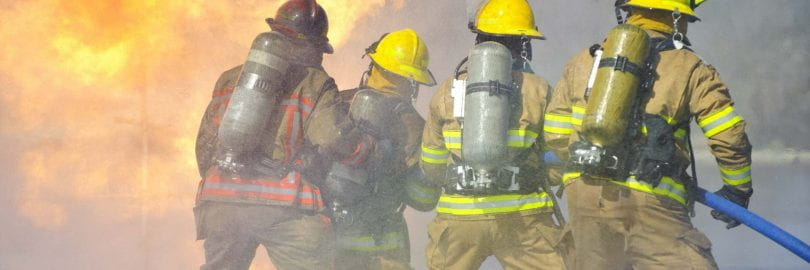 Four firefighters use a hose to battle a fire.