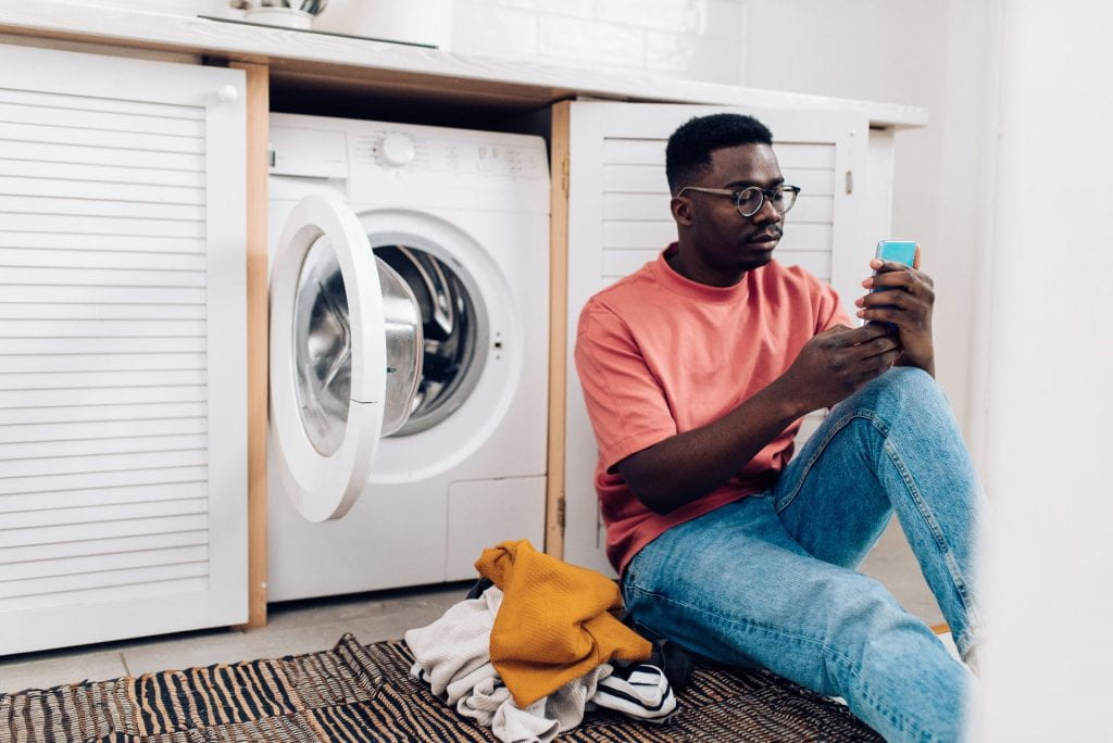 A young person reads their phone next to the clothes dryer while waiting for laundry to dry, a common activity for many college students returning from home from school during breaks.