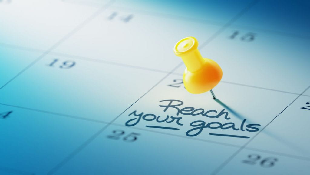 A calendar with a push pin placed on a date with the reminder ''reach your goals'', emphasizing the importance of following a calendar to predict stressors on college students.