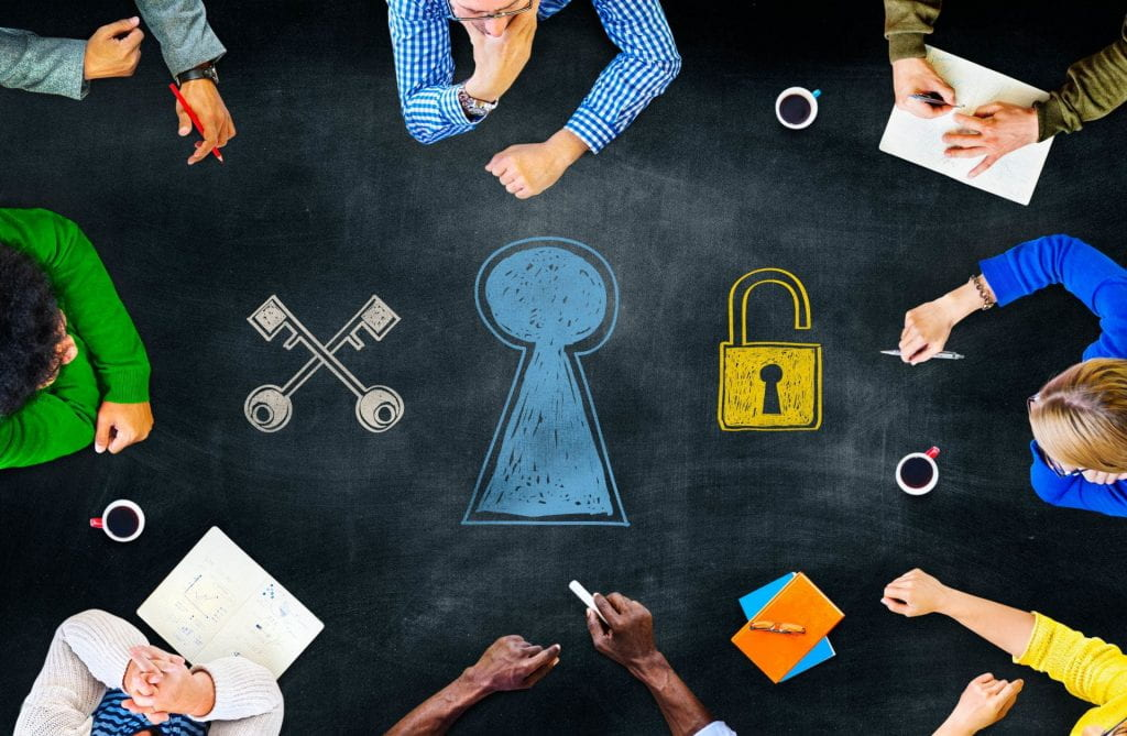 An image of people in a meeting with a key, and an open lock.