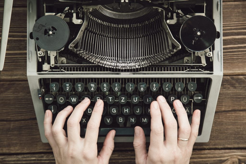An image of a typewriter and hands typing.