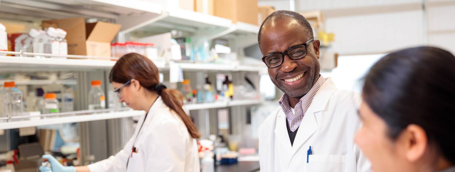 Gabriel Mbalaviele, PhD, works with members of his lab in the Institute of Health building.
