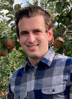 A man with brown hair and hazel eyes standing in front of an apple tree. His hair is medium length, but is put up in the front. He is wearing a blue flannel.