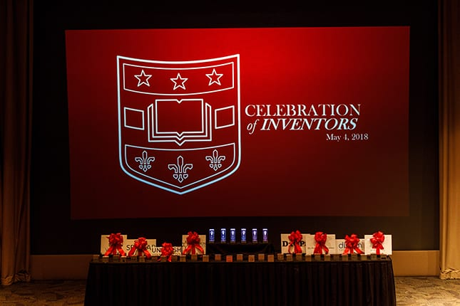 "Image of table with various awards; in background is a large projection screen with Washington University shield logo and text reading ""Celebration of Inventors, May 4, 2018""."