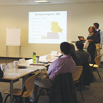 CCHP members look at a presentation slide in a conference room
