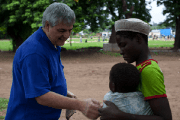 Dr. Manary speaks with a mother holding her child in a village in Malawi.