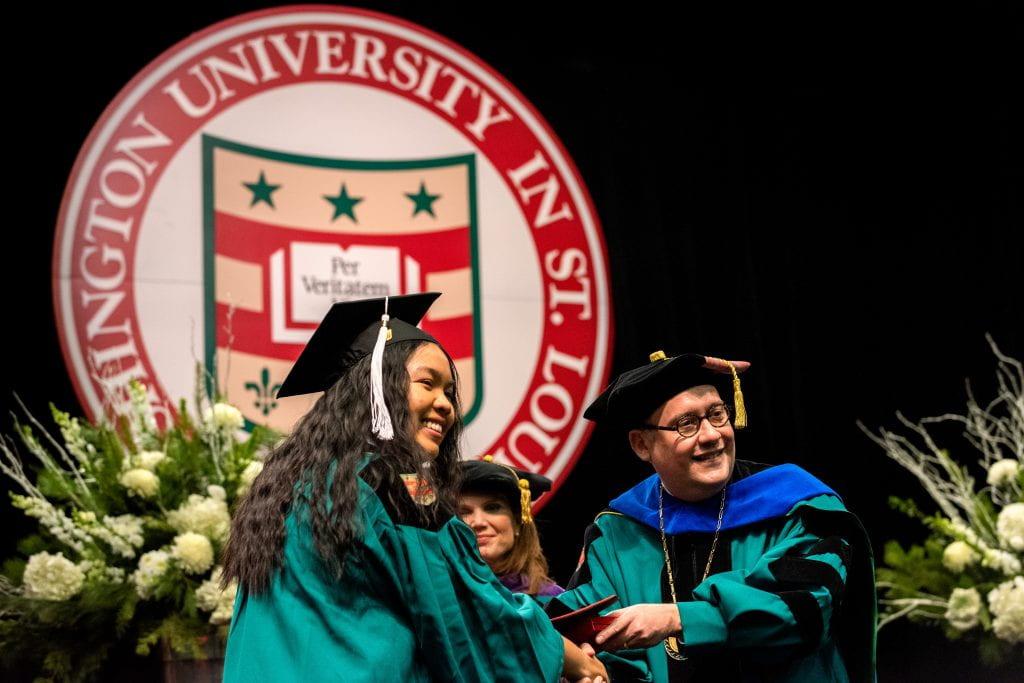 Alexis Pinzon (left) receives a degree from Chancellor Andrew Martin