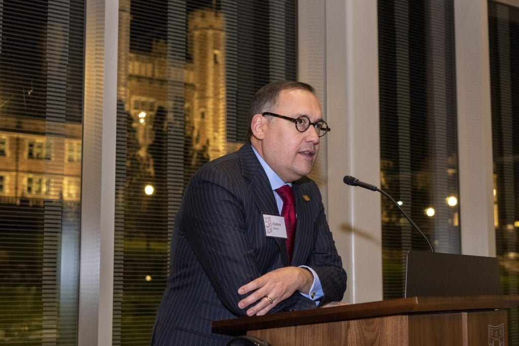 Andrew Martin at lectern with Brookings Hall in background through the glass at night.