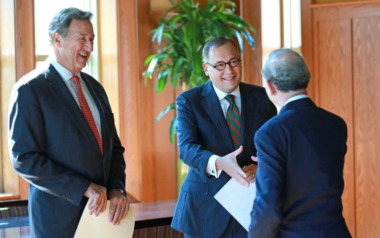 Andrew D. Martin shakes hands with Mark S. Wrighton as Craig Schnuck looks on